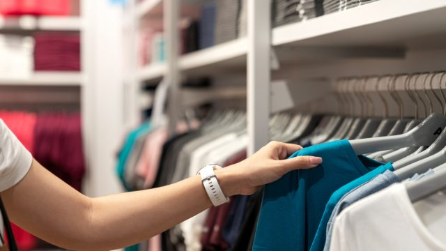 Close up of woman hand shopping or choosing casual blue color t-shirt on rack at department store