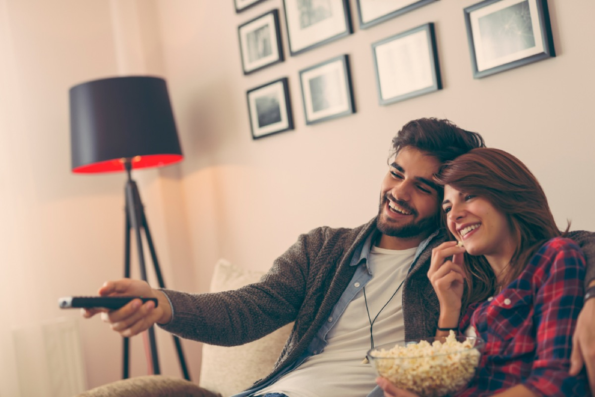 young man and woman watching tv and eating popcorn on the couch