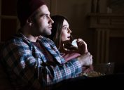 white man and white woman watching a movie with popcorn on their couch
