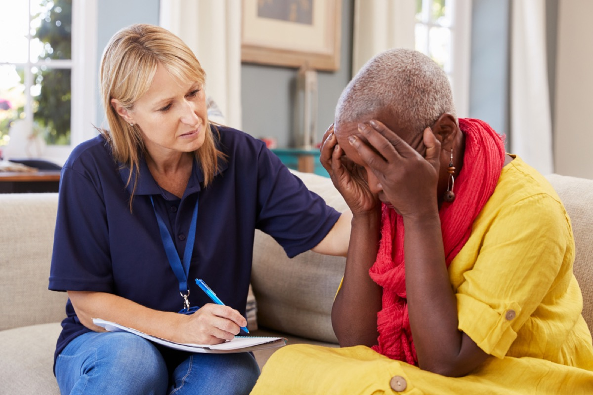 older black woman with head in hands talking to doctor