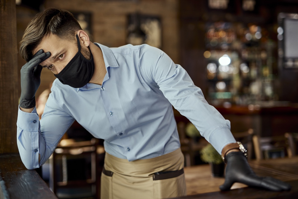 Distraught waiter holding his head in pain while wearing protective face mask and working in a pub.