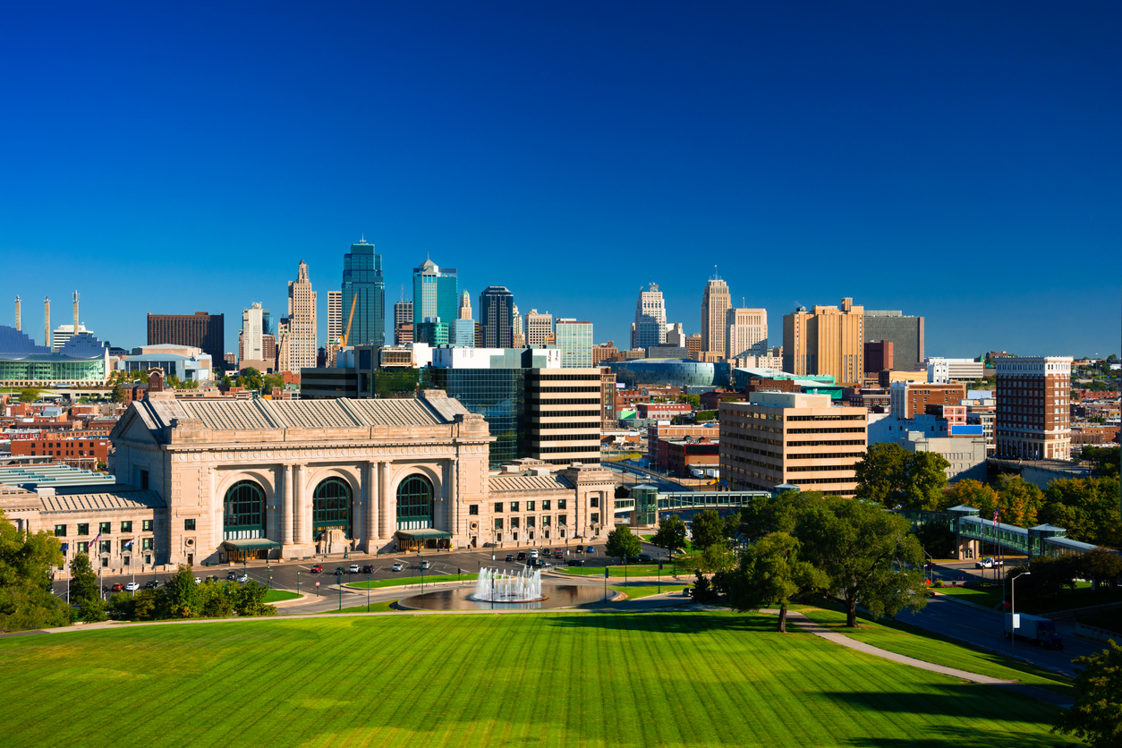 The skyline of Kansas City Missouri with a deep blue sky in the background and Union Station, a fountain, and Penn Valley Park in the foreground.