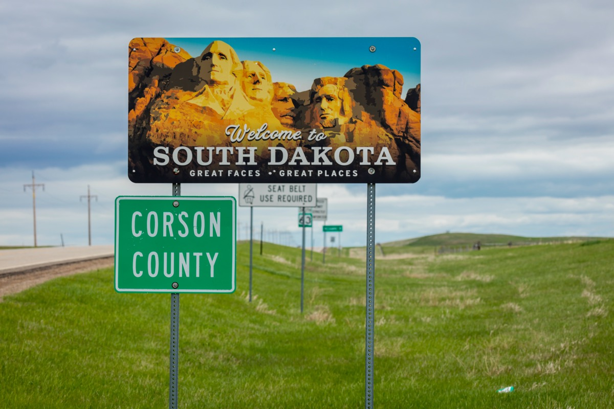 """A road sign featuring Mount Rushmore and that says """"Welcome to South Dakota"""" on it"""
