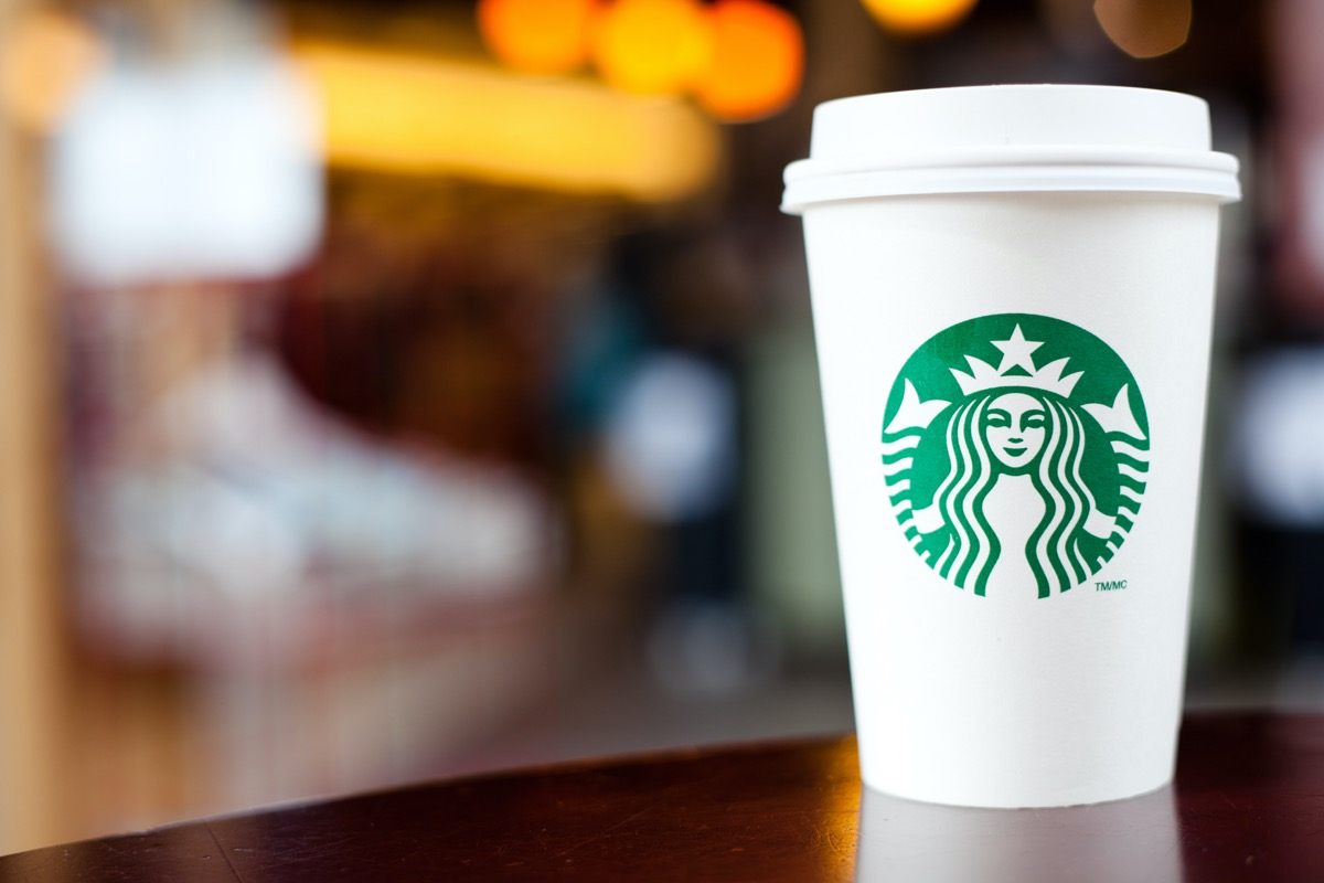 """""""Halifax, Nova Scotia, A!anada - September 18, 2011: A Grande Starbucks to go cup sitting on a table. Starbucks is a very popular International Coffeehouse franchise with over 15,000 locations in 50 countries"""""""