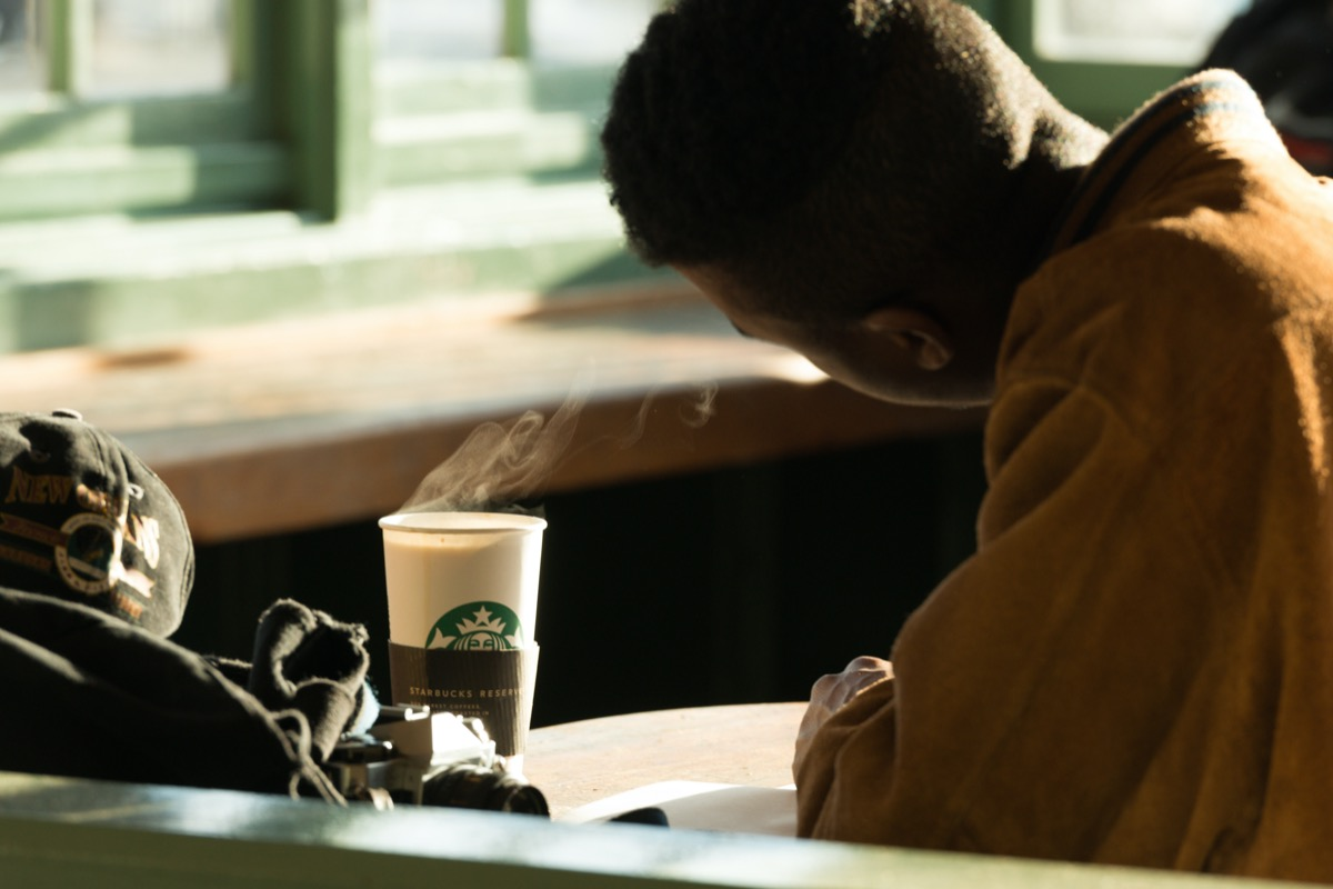A man In Pike Place Market late in the day with a hot cup of Starbucks coffee.