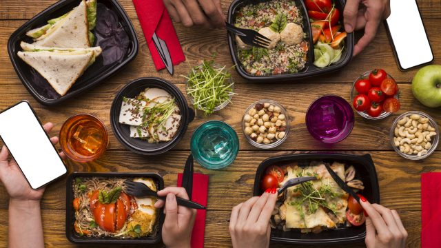 An above shot of takeout food in containers on a table as people eat.