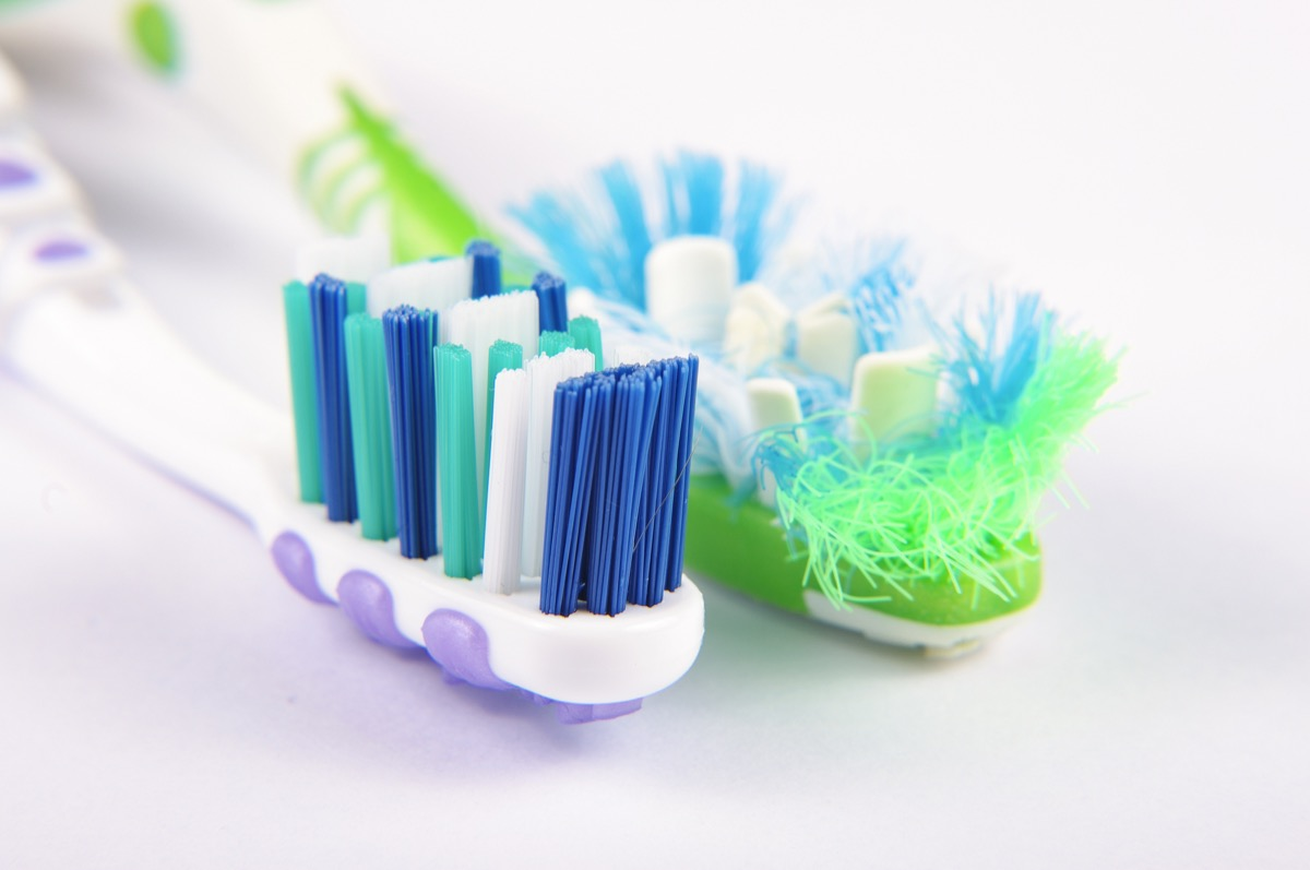 Old, frayed toothbrush next to brand new toothbrush