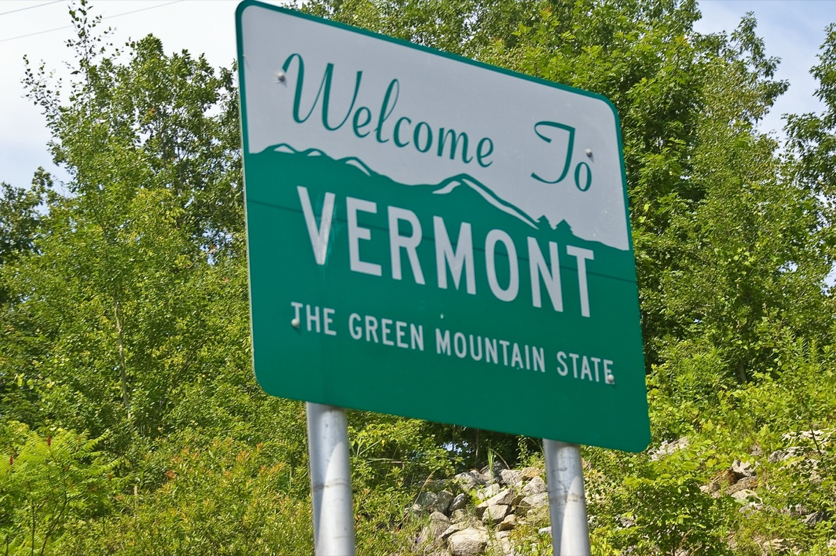 """a green """"Welcome to Vermont"""" sign in front of green trees"""