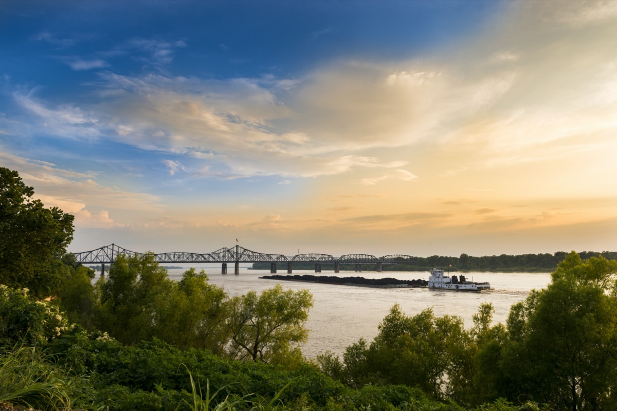 a white boat in and a bridge over the Mississippi River in Vicksburg, Mississippi