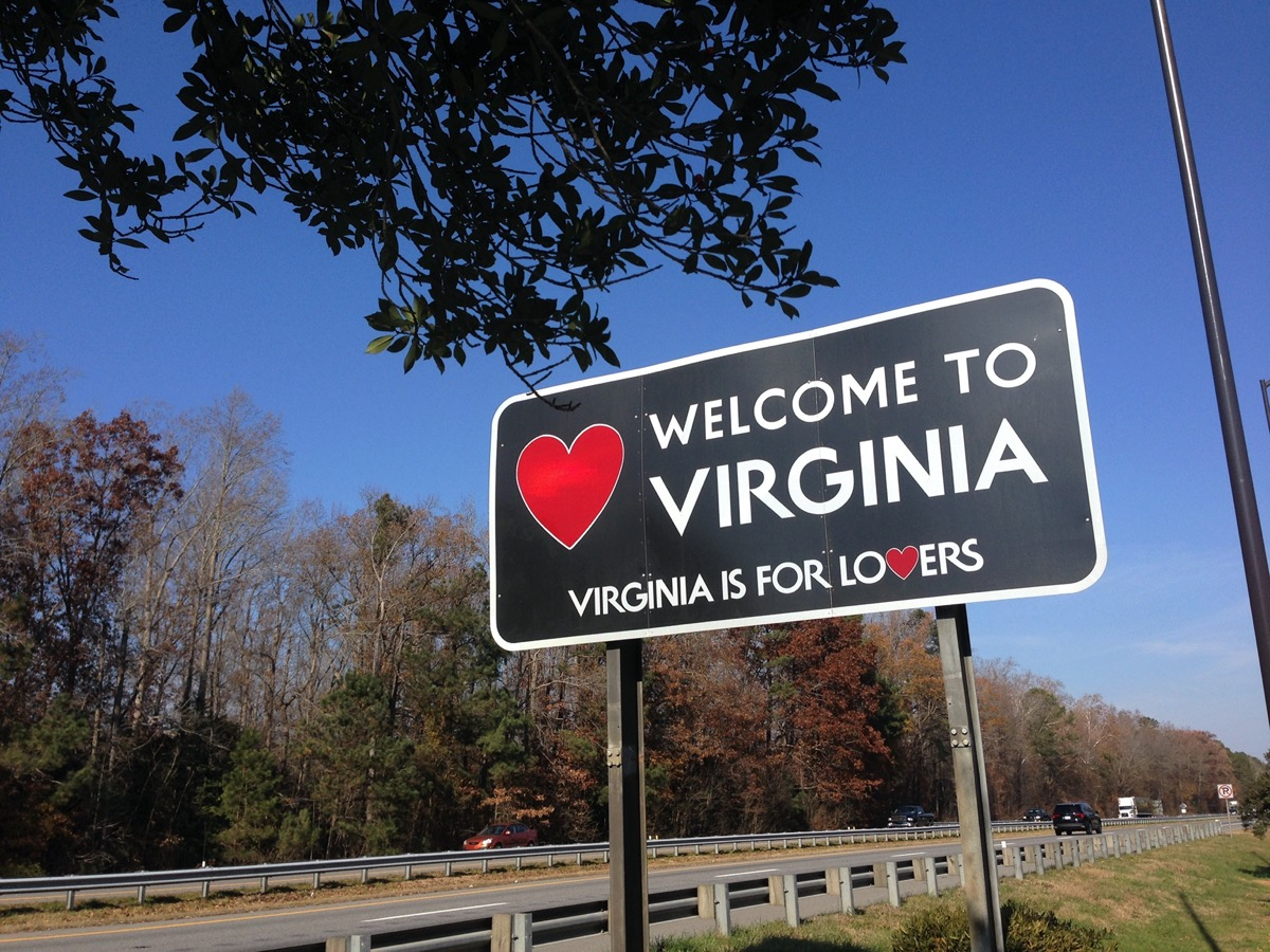 """a black """"Welcome to Virginia"""" sign off of a highway"""