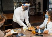 A waiter at a high-end restaurant wearing a face mask and face shield approaches the table carrying a tray, serving to women who are seated and wearing face masks.