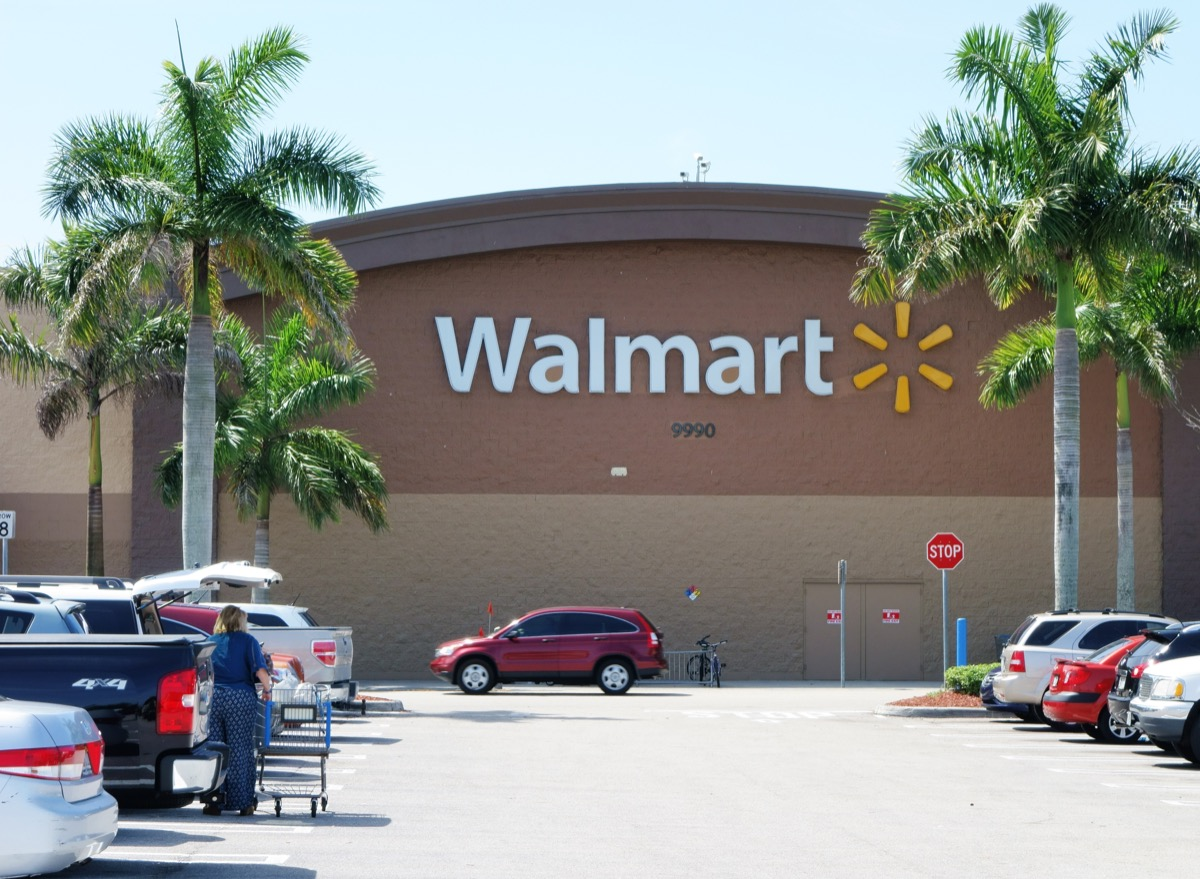 A Walmart store with a full parking lot. Walmart is the largest retailer in the world and operates thousands of large discount department stores. A woman customer empties her shopping cart into a car in the parking lot.