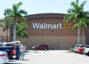 West Palm Beach, USA - April 3, 2014: A Walmart store with a full parking lot. Walmart is the largest retailer in the world and operates thousands of large discount department stores. A woman customer empties her shopping cart into a car in the parking lot.