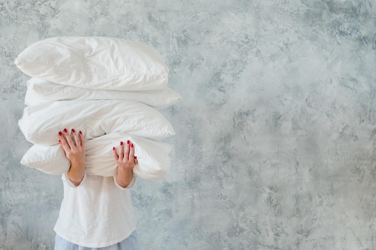 woman hold pile white pillows bedding sleeping