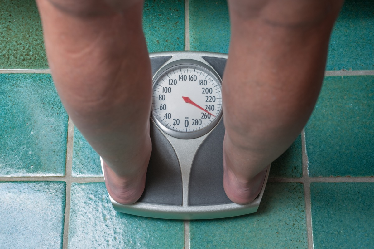 Person weighing themselves on scale because of weight loss