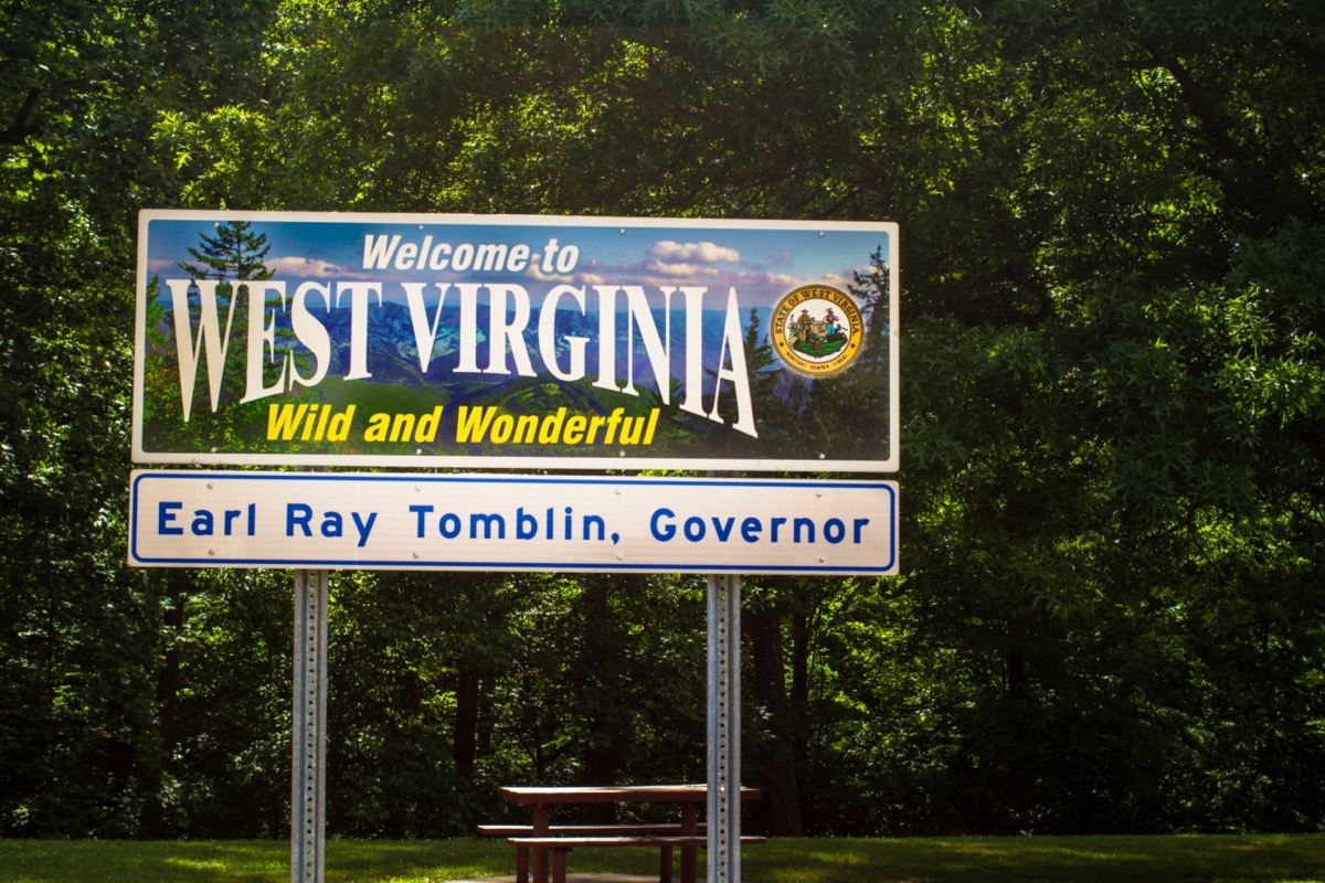 """a """"Welcome to West Virginia"""" sign in front of green trees"""