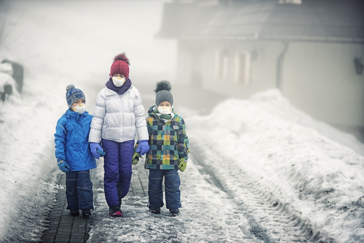 three children walking in the snow while wearing masks and winter hats and coats