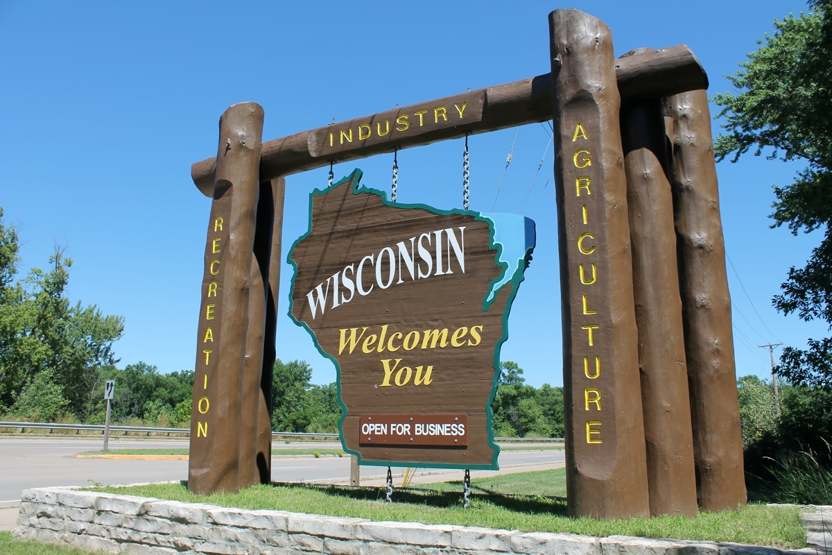 """a tall and wooden """"Wisconsin Welcomes You"""" off of a highway"""