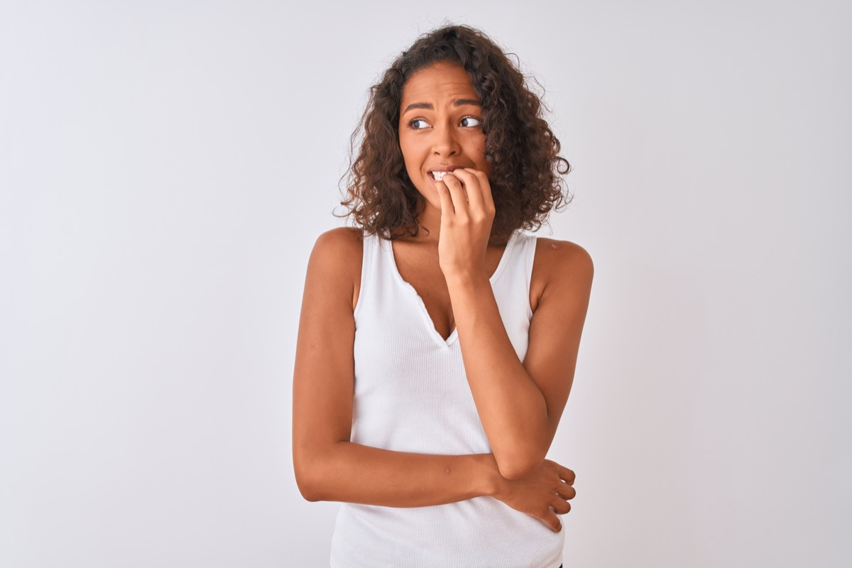 Young brazilian woman wearing casual t-shirt standing over isolated white background looking stressed and nervous with hands on mouth biting nails. Anxiety problem.