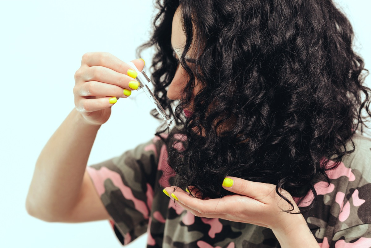 young woman applying hair oil to curls