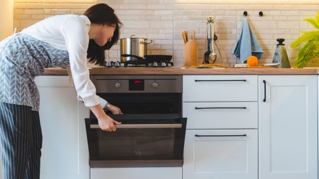 A woman wearing an apron checks inside the oven in her kitchen