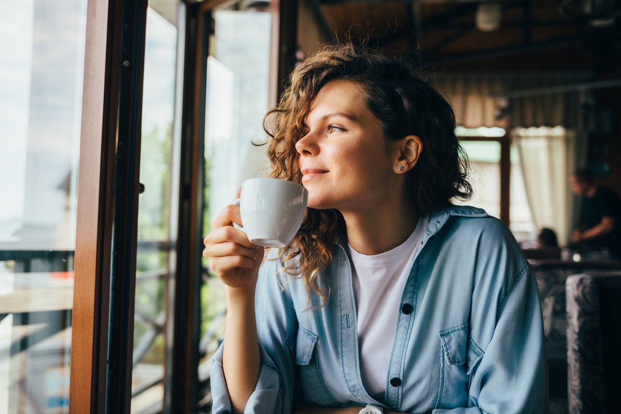 A smiling young woman drinking coffee while looking out the window.