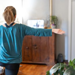 A young woman works out in her living room to a class on her laptop