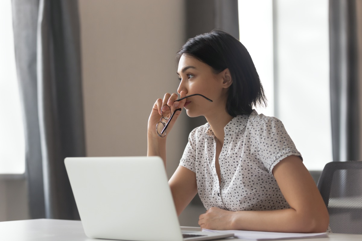 Thoughtful anxious business woman looking away thinking solving problem at work, worried serious young chinese woman concerned make difficult decision lost in thought reflecting sit with laptop