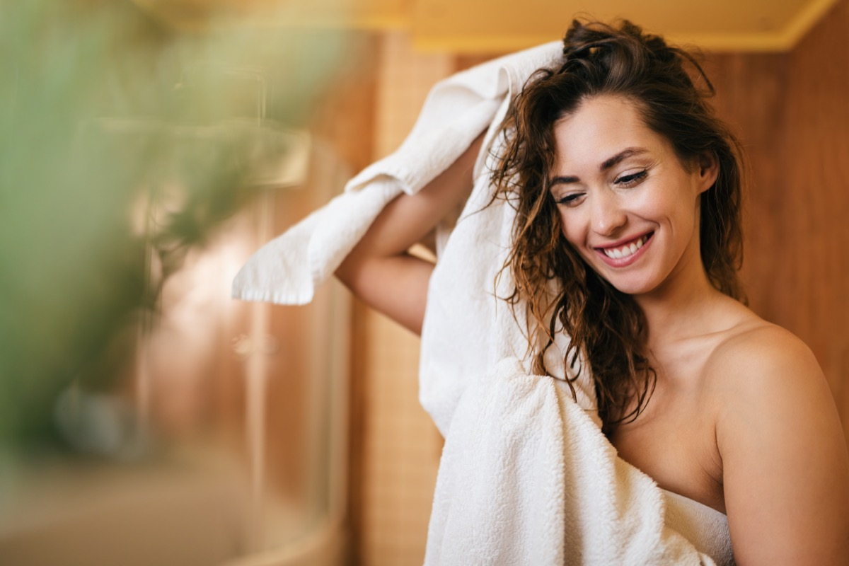 Young beautiful woman using towel and drying her hair in the bathroom.