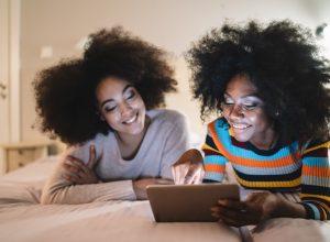 Friends using digital tablet in bed