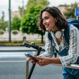 Young woman is standing on the street and leaning on her electric scooter while using smart phone and smiling