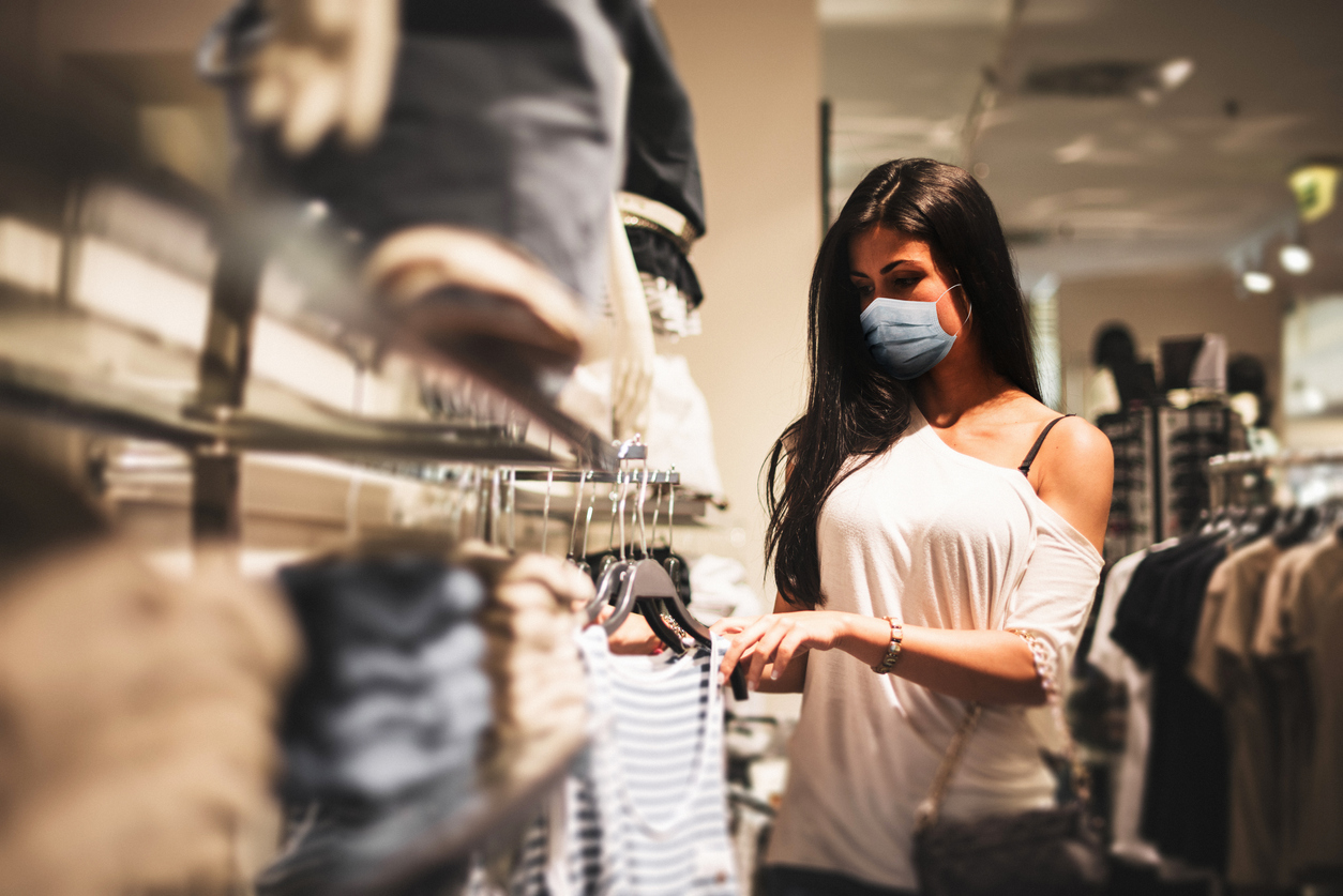 A young woman wearing a face mask shopping in a retail clothing store amid the coronavirus pandemic