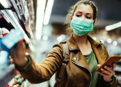 young white woman shopping wearing surgical mask