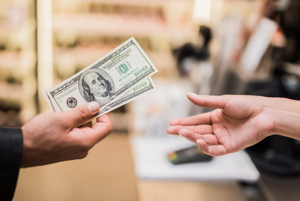 man paying with cash in store