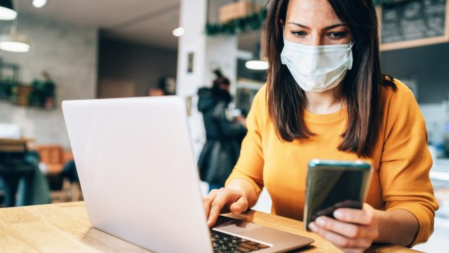 A young woman in a yellow sweater checks her smartphone while using her laptop and wearing a face mask