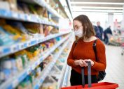 A young woman wearing glasses and a face mask shops in a supermarket