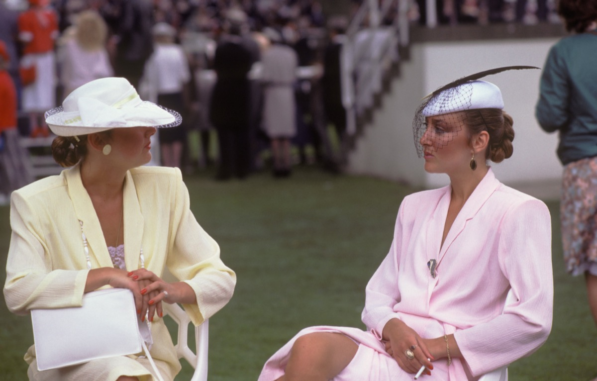 women sitting outside wearing pastel suits with large shoulder pads