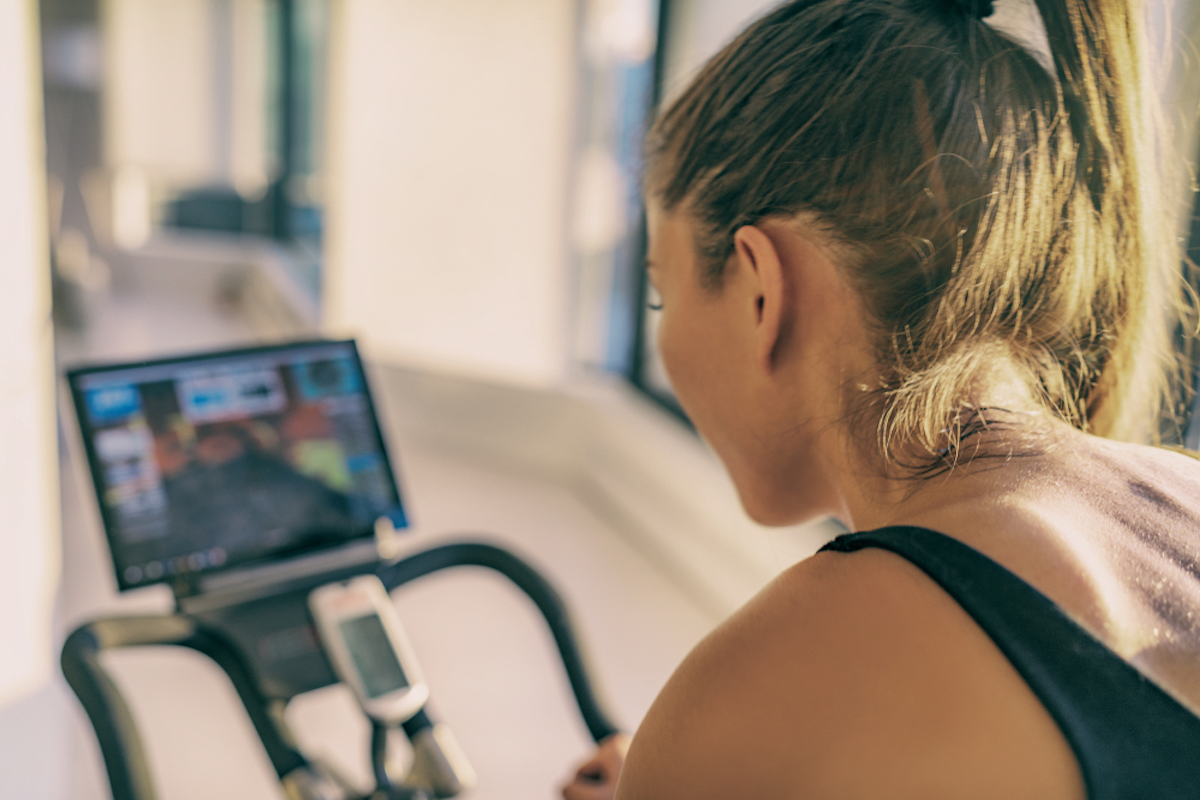 woman training on stationary bike equipment indoors while watching class on screen