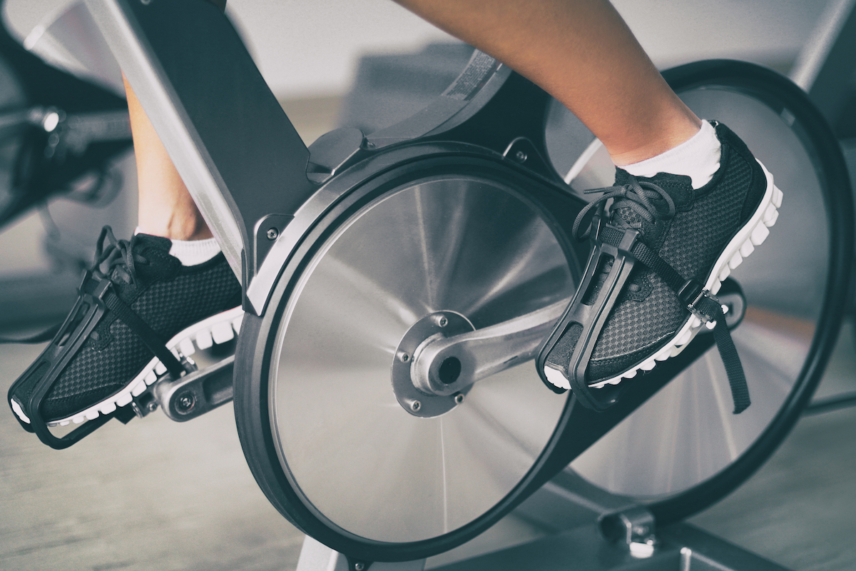 closeup of person biking on indoor cycling stationary bike at home with feet in pedals