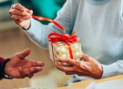 Close-up shot of a lovely senior couple exchanging christmas gifts in dining room.