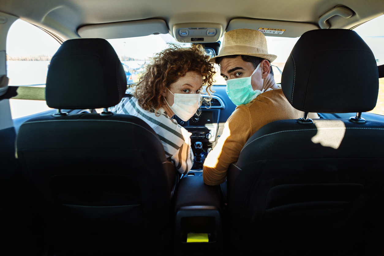 A young couple wearing face masks in a car look back from the front seat to the back seat