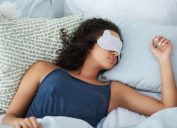 A young woman sleeping in in the morning wearing a cat-shaped eye mask
