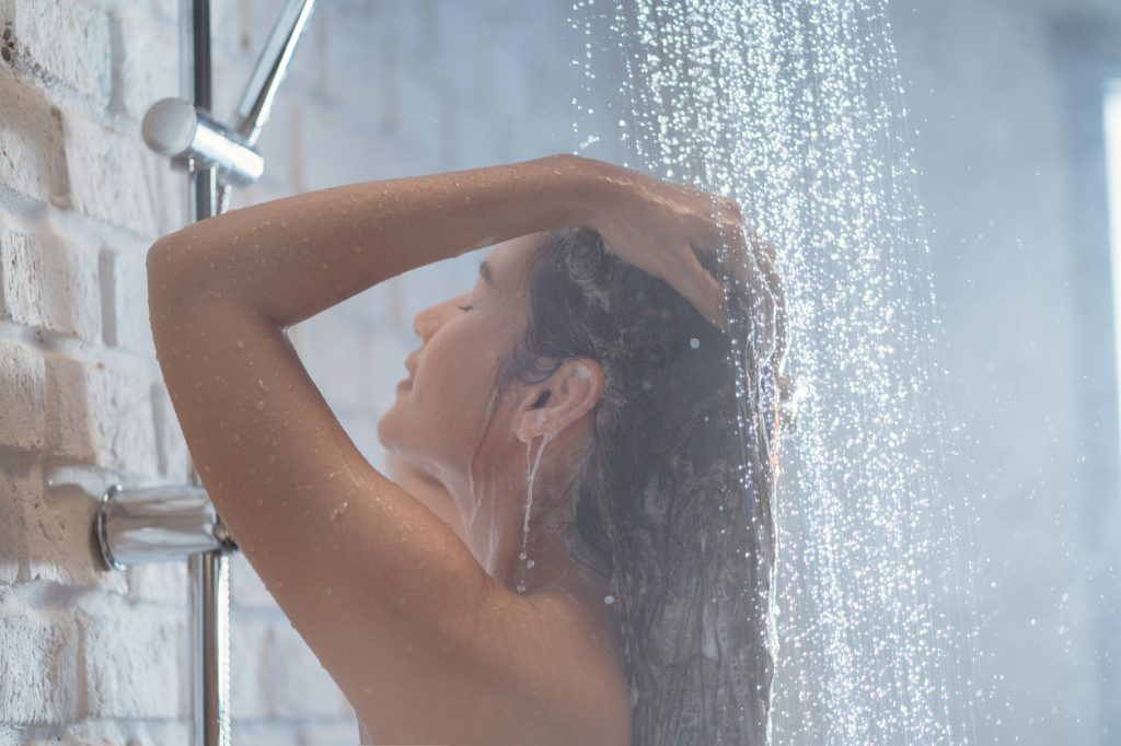 A young woman washing her hair while showering
