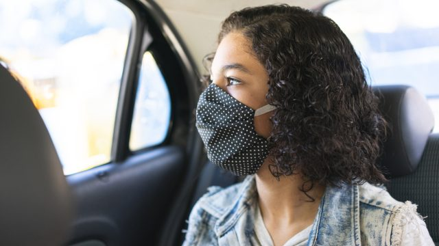 A young woman wearing a face mask in the back seat of a car