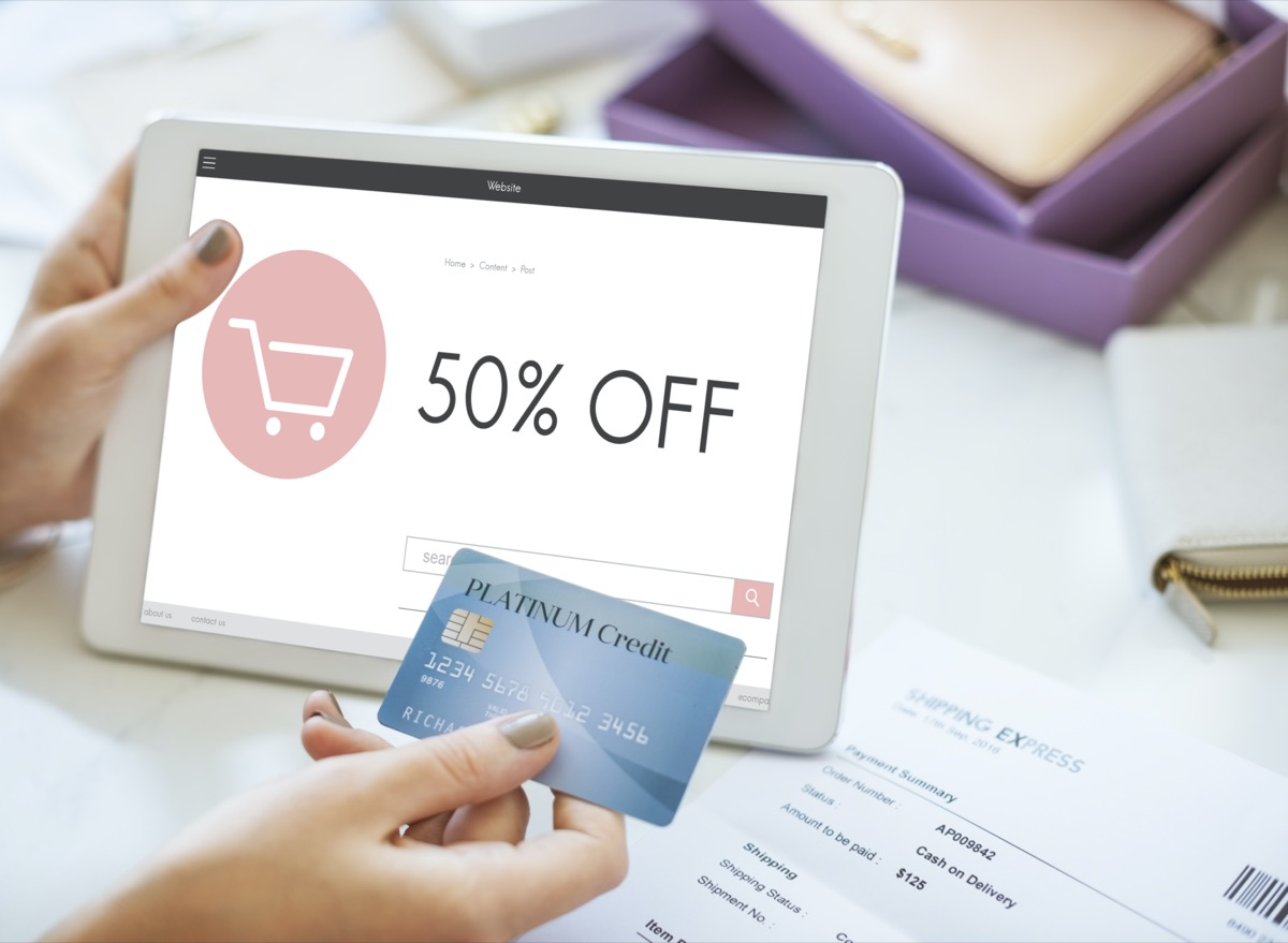 tablet showing a '50% OFF' sign on a website and hand holding a credit card