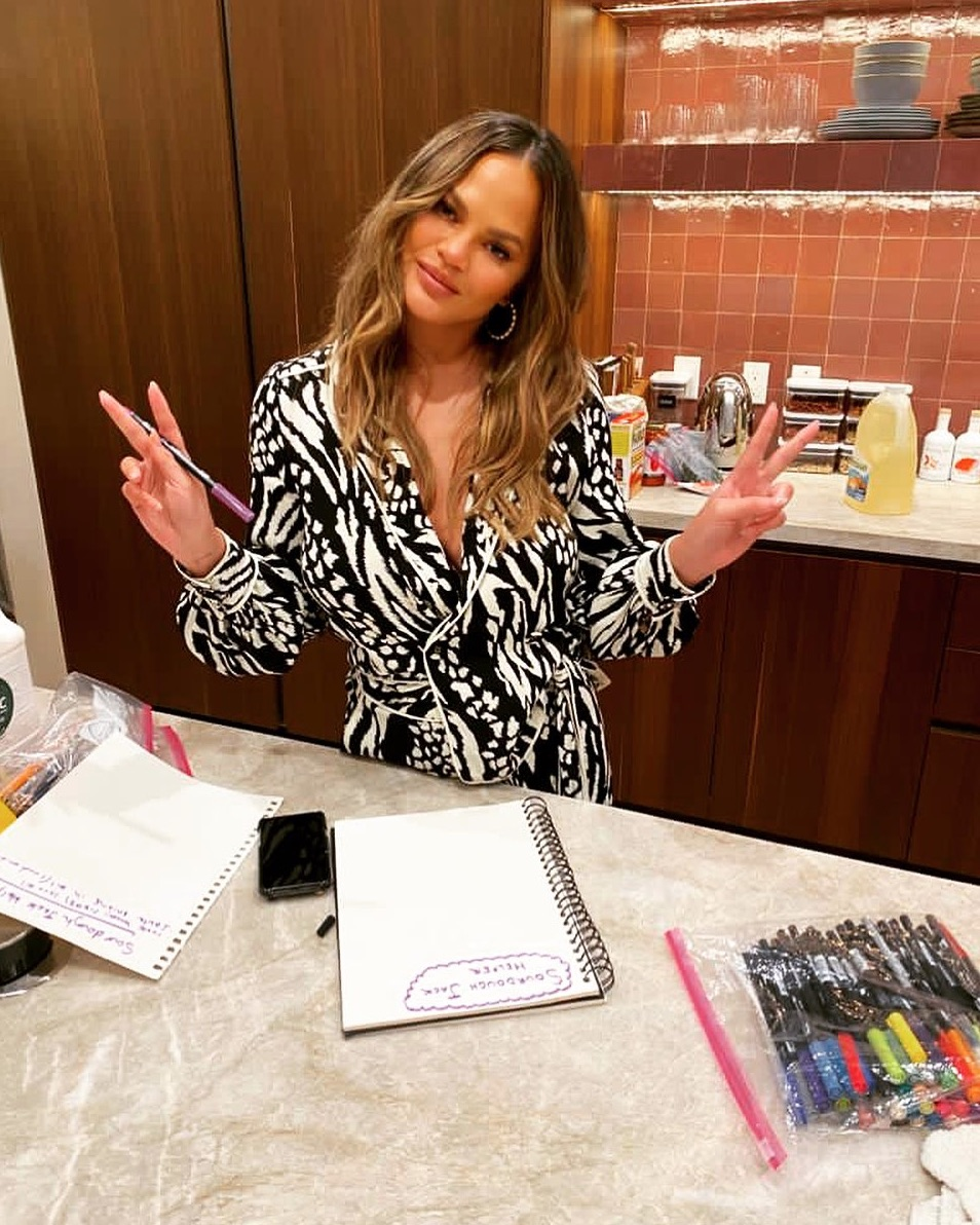 Chrissy Teigen posing with peace signs on Instagram
