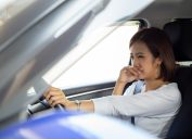 Young Asian woman hold her nose because of bad smell in car