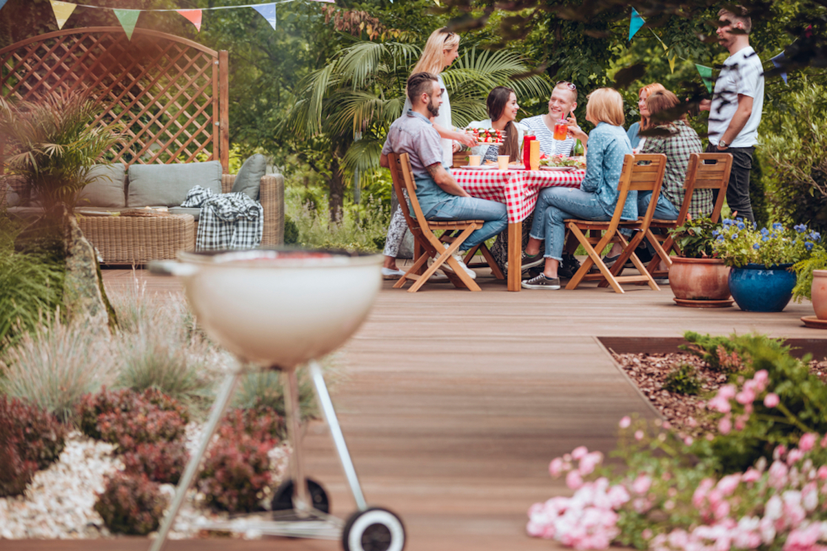 barbecue with people eating outside in the background