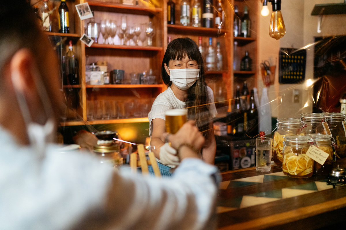 A bar owner is giving beer to customer from behind a protective clear plastic curtain while wearing a mask