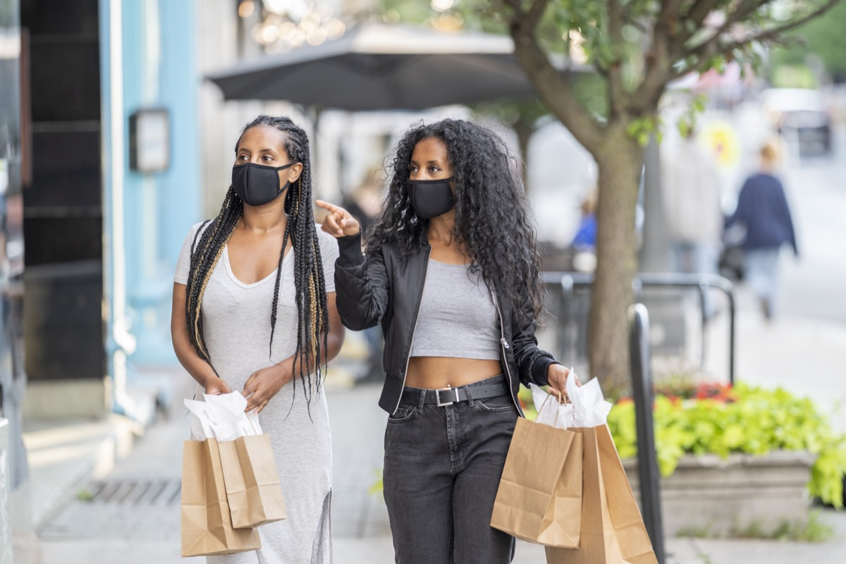 Two woman walking downtown, holding shopping bags, and doing some window shopping while wearing protective face masks during the COVID-19 pandemic.